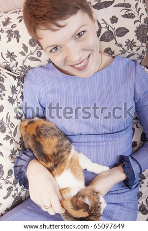 Young woman playing on a sofa with a little cat - stock photo