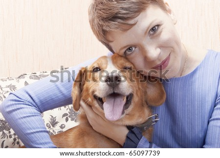 Young woman playing on a sofa with her joyful dog - stock photo