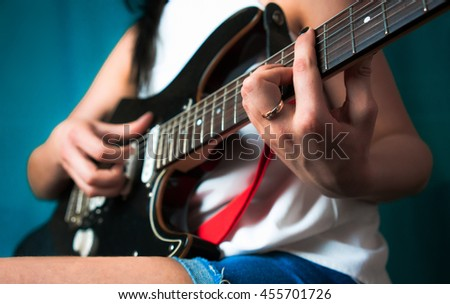 Young woman playing on guitar. close up - stock photo