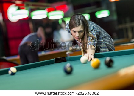 Young woman playing pool - stock photo