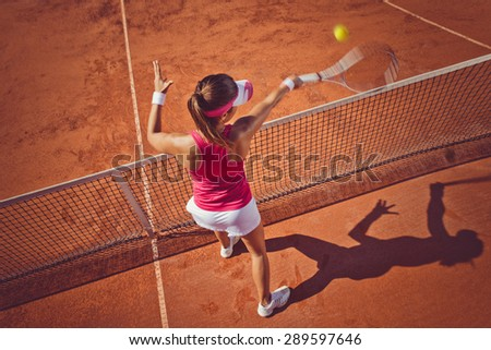 Young woman playing tennis.High angle view.Forehand volley. - stock photo