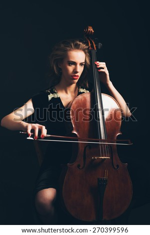 Young woman playing the cello in a classical concert or recital sitting in the darkness with a serious expression as she awaits her cue to start playing - stock photo