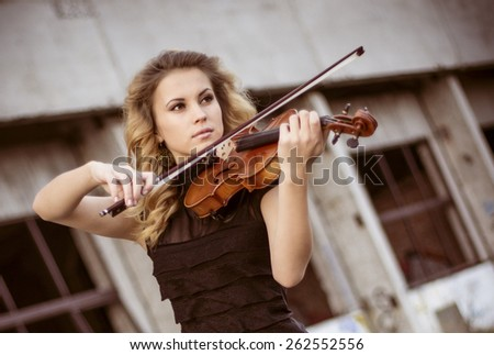 Young woman playing the violin at outdoors. Shallow depth of field. - stock photo