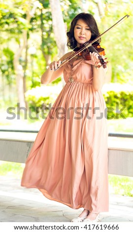 Young woman playing violin in garden - stock photo