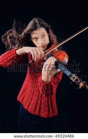 Young woman playing violin. Isolated on the black background - stock photo