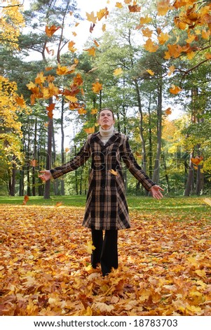 Young woman playing with autumn leafs
