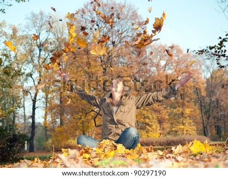 young woman playing with autumn leaves - stock photo