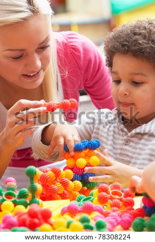 Young woman playing with boy - stock photo