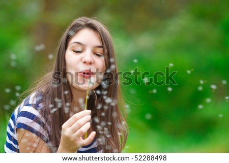 Young woman playing with dandelion in the grass - stock photo