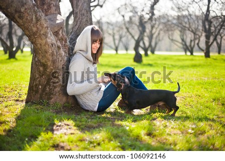 young woman playing with dog dachshund  in a park - stock photo