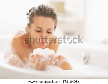 Young woman playing with foam in bathtub - stock photo