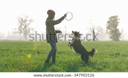 Young woman playing with her border collie dog. Concept about animals and dogs - stock photo
