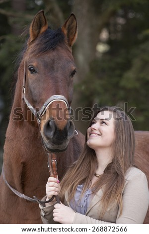 Young woman playing with horse - stock photo