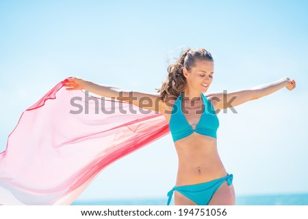 Young woman playing with parero on beach - stock photo
