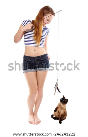 young woman playing with siamese cat and cat teaser with feathers - stock photo