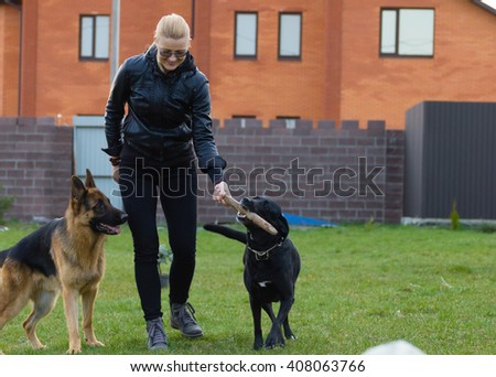 Young woman plays with a German shepherd and labrador outdoors