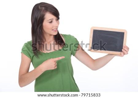 Young woman pointing at a blank blackboard - stock photo