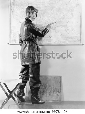 Young woman pointing at a map in a motorcycle outfit - stock photo