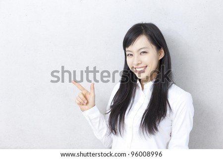 Young woman pointing copy space.