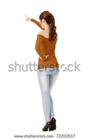 Young woman pointing, full length portrait from back isolated on white background. - stock photo