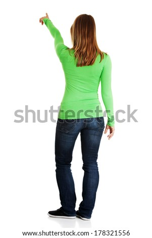 Young woman pointing on copy space, isolated on white  - stock photo