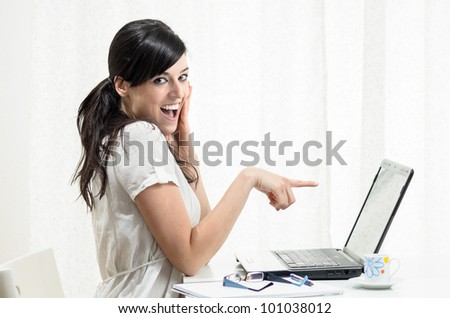 Young woman pointing the finger to the screen of her laptop while she touchs her face and shows surprise.