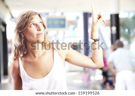 young woman pointing up in a shopping center - stock photo