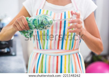 Young woman polishing a glass in her modern kitchen - stock photo