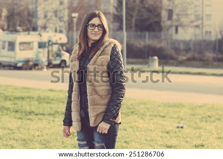 Young Woman Portrait at Park in the Morning. The Girl has a Piercing at upper lip and is Looking at Camera. The Park is in a Residential Area, there are some Houses on Background. - stock photo