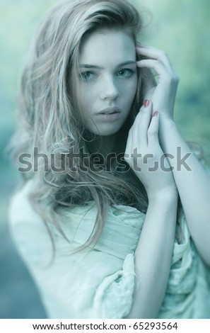 Young woman portrait. Cold aqua blue tint.