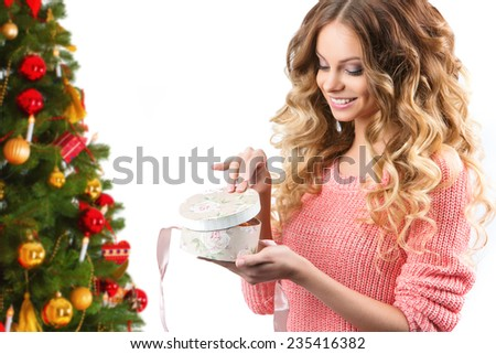Young woman portrait hold gift. Smiling happy girl on white background. Girl opens a gift against the background of the Christmas tree, Christmas holiday and New Year. - stock photo