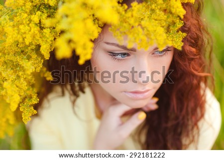 Young woman portrait in autumn color. The wreath of yellow flowers on the girl head.