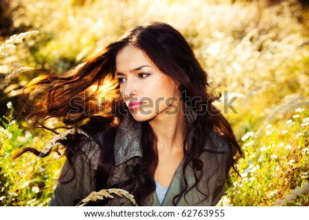 young woman portrait in autumn field, wind in hair - stock photo