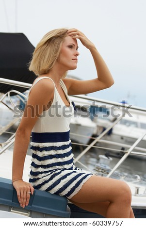 Young woman portrait near sea in summer day on yacht stop