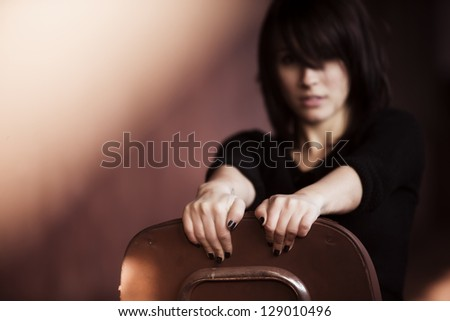 Young woman portrait showing attitude sitting on a chair. - stock photo