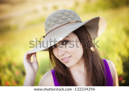 Young woman portrait wearing a big hat. - stock photo
