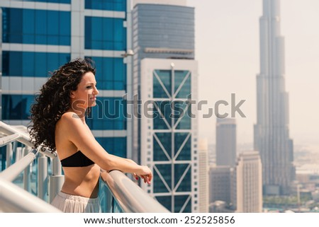 Young woman portrait wearing bikini sunbathing in swimming pool in Dubai. Filtered image  - stock photo