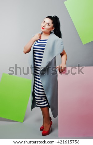 Young woman portrait with blank pink and green banner, board on gray isolated. - stock photo