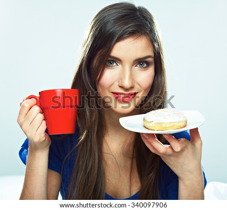 Young woman portrait with donut and coffee cup. Beautiful female model with long hair. - stock photo