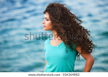 young woman portrait with long curly hair windy day by the sea summer time