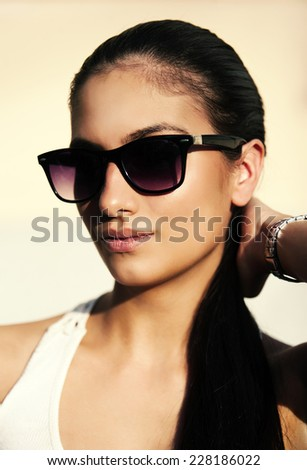 Young woman portrait with sun glasses and pony tail