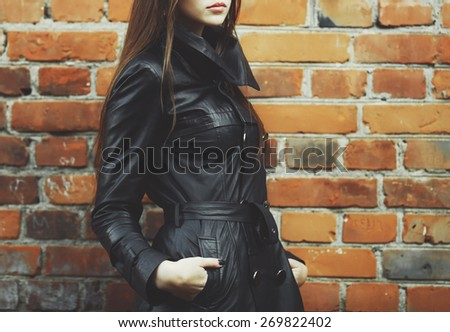 Young woman posing against break wall, wearing leather jacket.  - stock photo