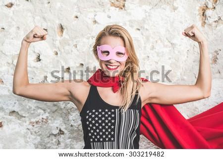 Young woman posing as superhero or superwoman - stock photo
