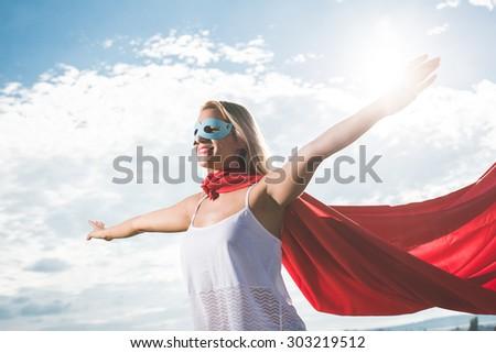 Young woman posing as superhero over blue sky - stock photo