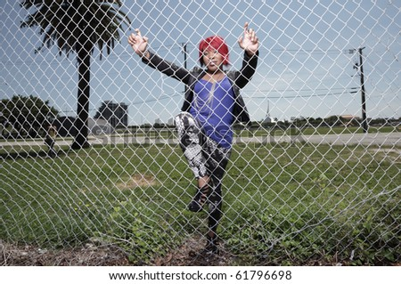 Young woman posing by a fence - stock photo