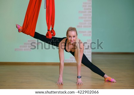 Young woman posing doing aerial yoga exercise with hammock