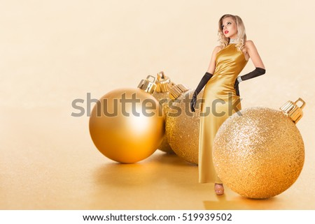 Young woman posing for fashion portrait in a golden dress next to some giant christmas decoration balls