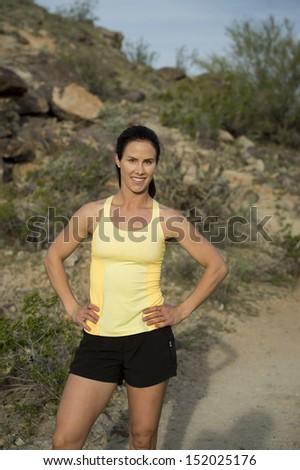 Young woman posing for the camera before her trail run outdoors at South Mountain Park in Phoenix, Arizona.