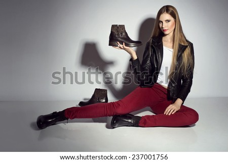young woman posing in leather jacket and boots  - stock photo