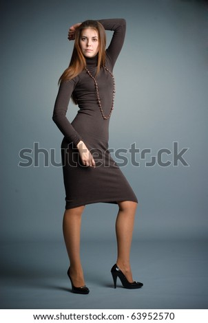 young woman posing in studio in a cute dress